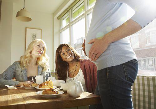 Women admiring friends pregnant belly.