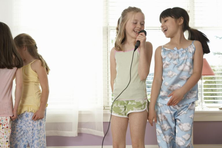 Four girls (8-10) at slumber party, two girls singing into microphone