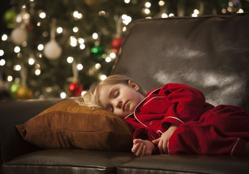 Child sleeping on a sofa in front of a Christmas tree
