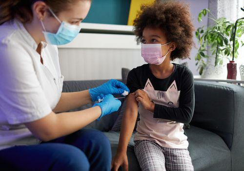 A young child gets vaccinated by a nurse on a couch.