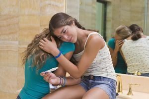 Two teen girls holding pregnancy test in bathroom