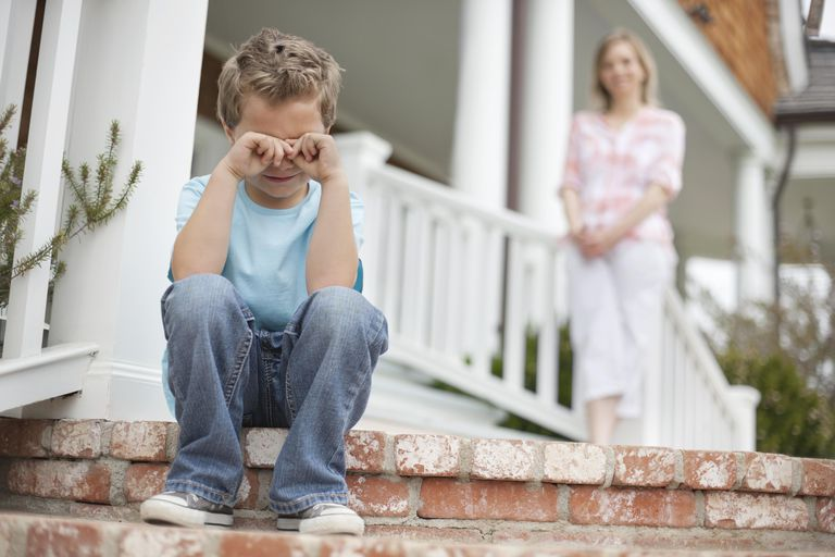 Boy sitting on porch crying, mother in background
