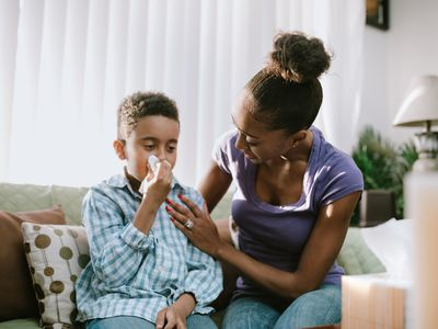 mother and her son sitting on the couch, the son is blowing his nose