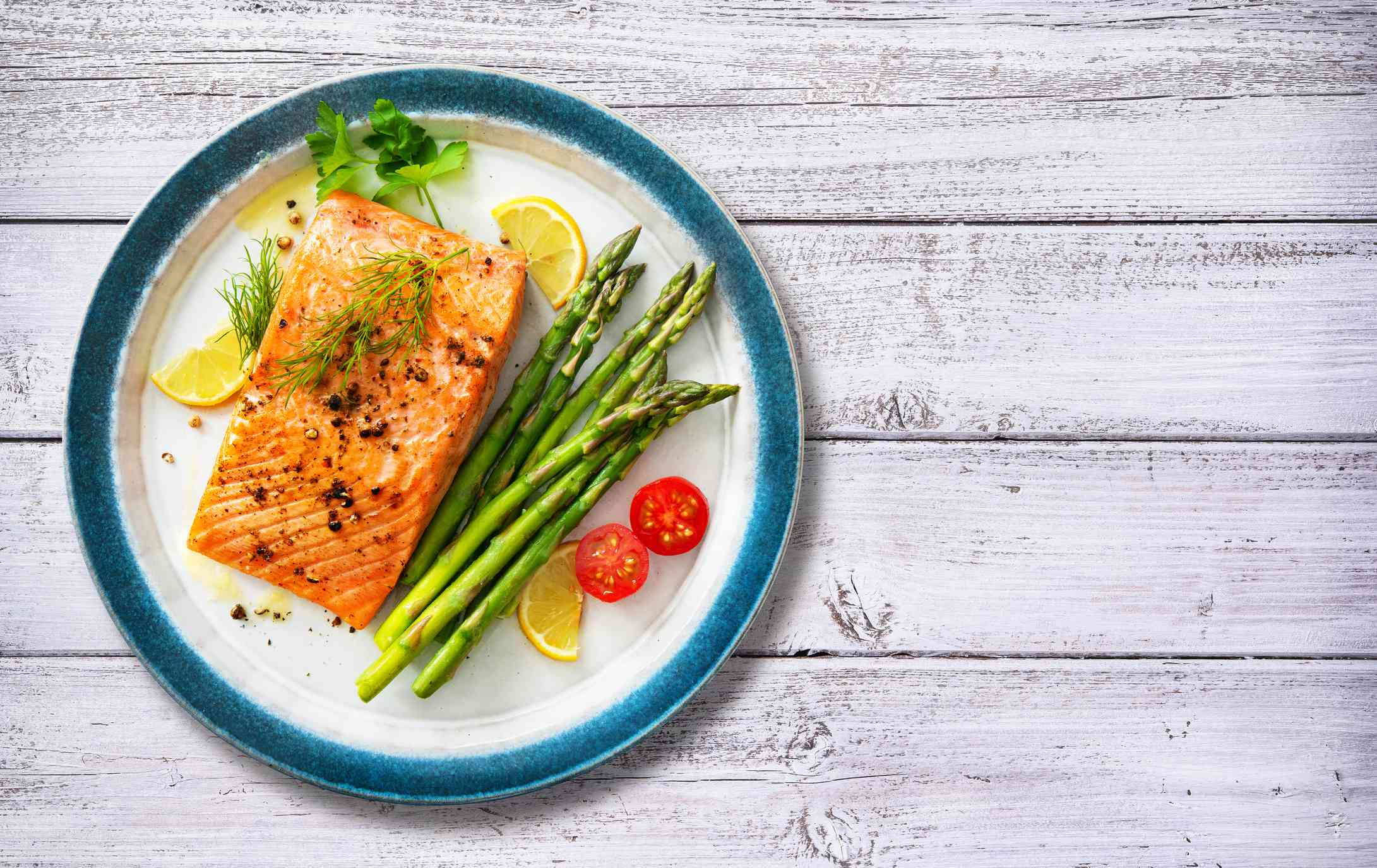 Grilled salmon steak garnished with green asparagus, lemon and tomatoes