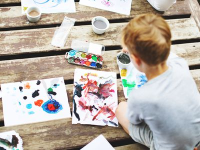 boy painting outside on deck