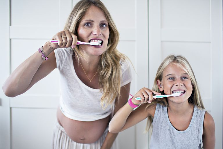 Pregnant woman brushing teeth with daughter