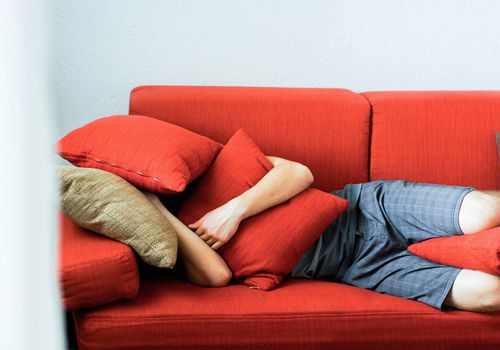 Teenage boy lying on couch with cushions over his face