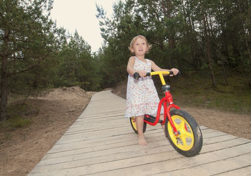 A preschooler riding a bike without shoes.