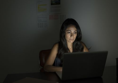 Woman sitting at computer in darkened room buying Clomid online