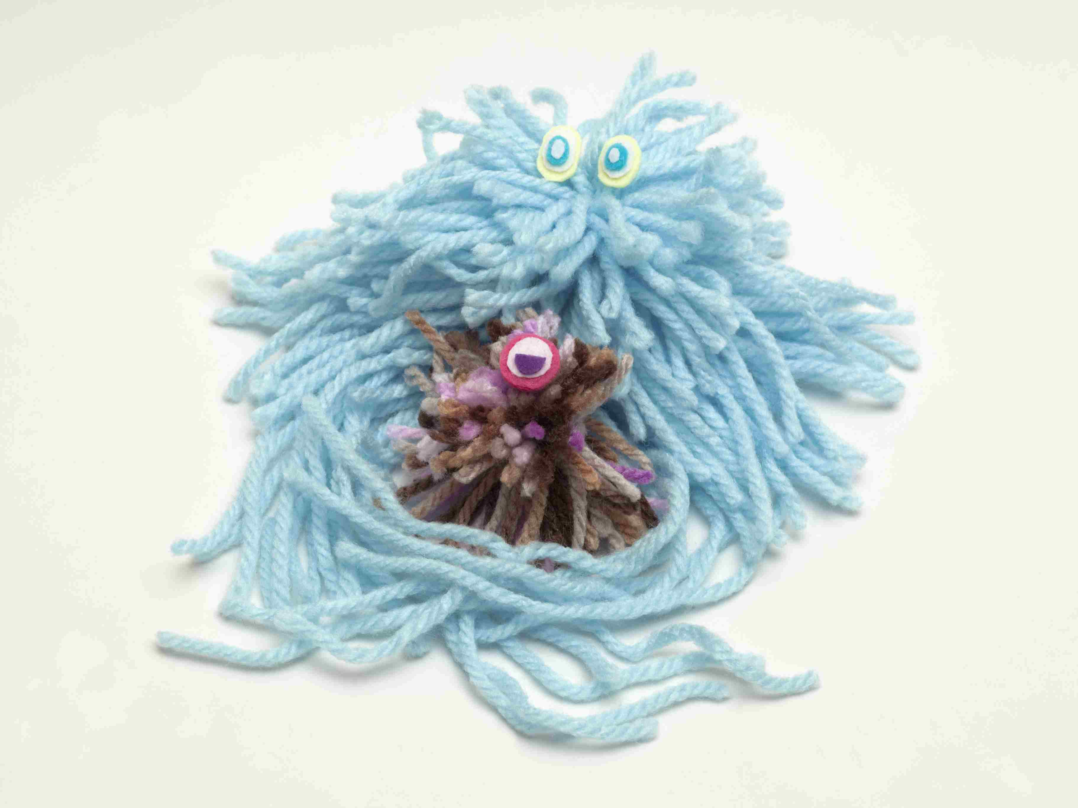 Wool doll natural killer cell engulging a wool cancer cell