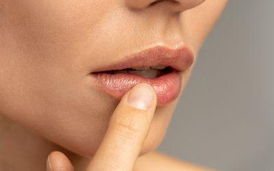 Woman applying lip balm to dry lips