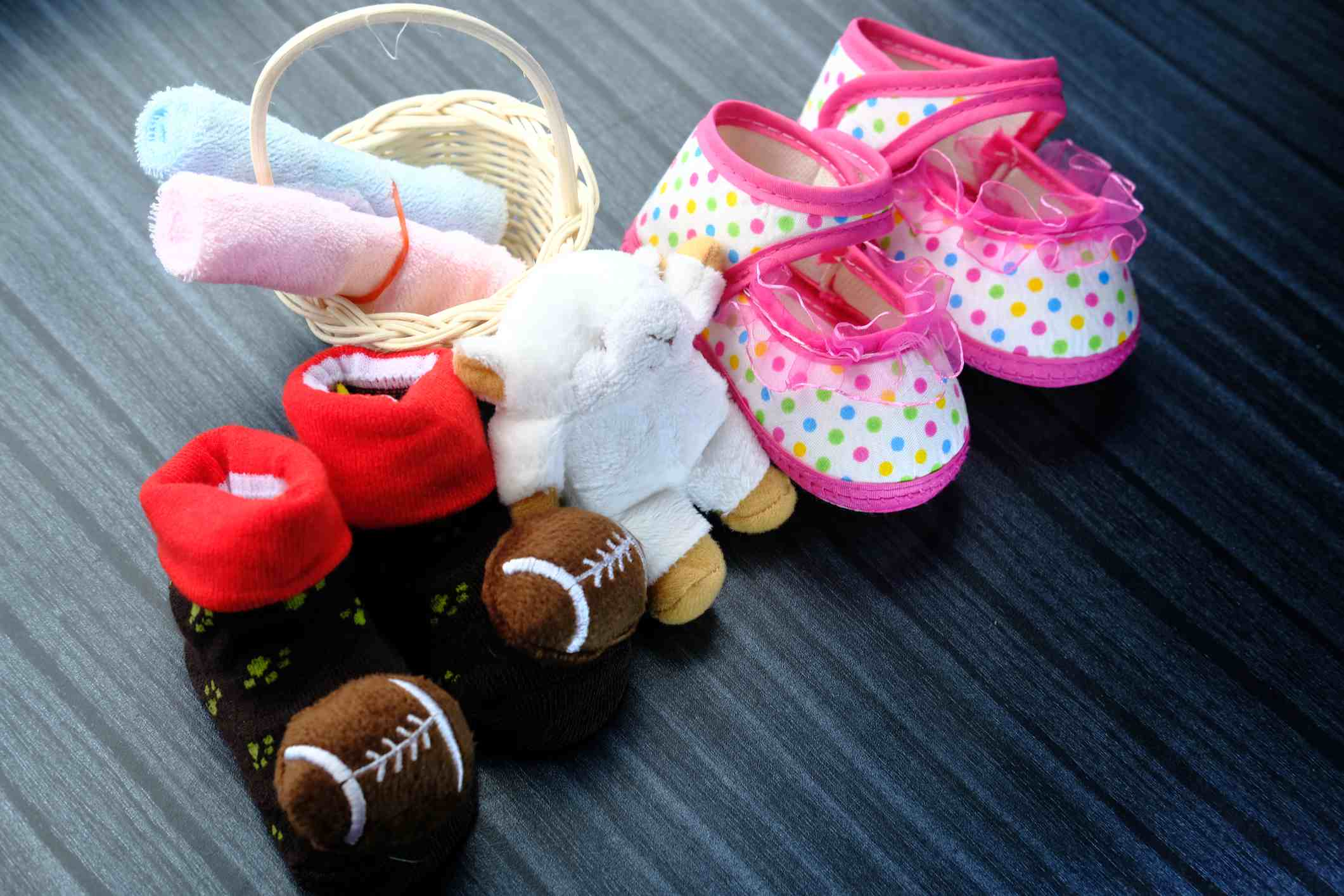 Two pairs of baby booties and a stuffed animal