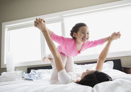 Girl playing airplane with mom on a bed