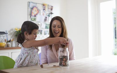 Mother and daughter (3-4) putting coins into jar