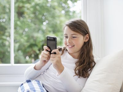 Girl (10-11) texting on mobile phone