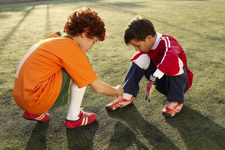 Boy (8-9) helping friend (6-7) to tie shoestrings