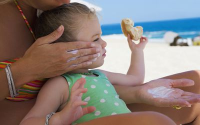 Woman applying suntan lotion to her little girl on a beach