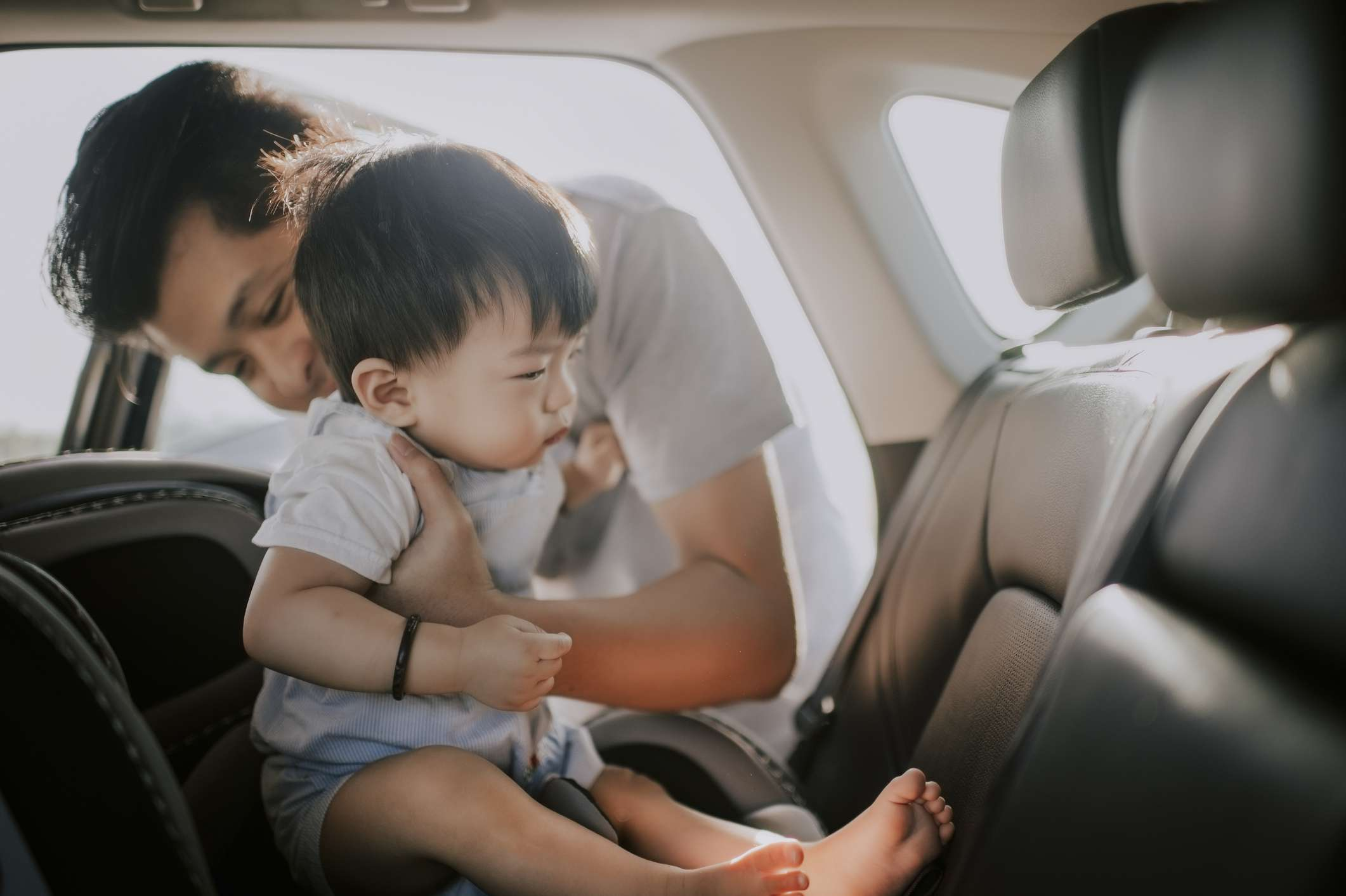 Father putting his toddler into carseat