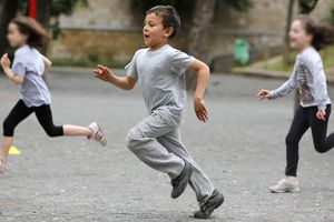 Boy running outside with two girls in background