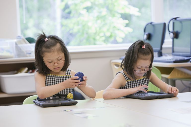 Mixed race Down syndrome students using tablet computers in classroom