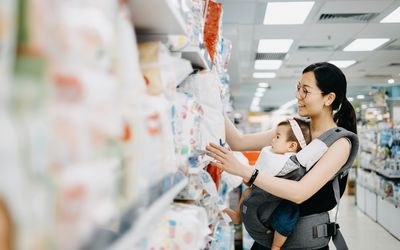 Woman shopping for diapers with her baby