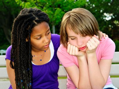 young girl comforting another