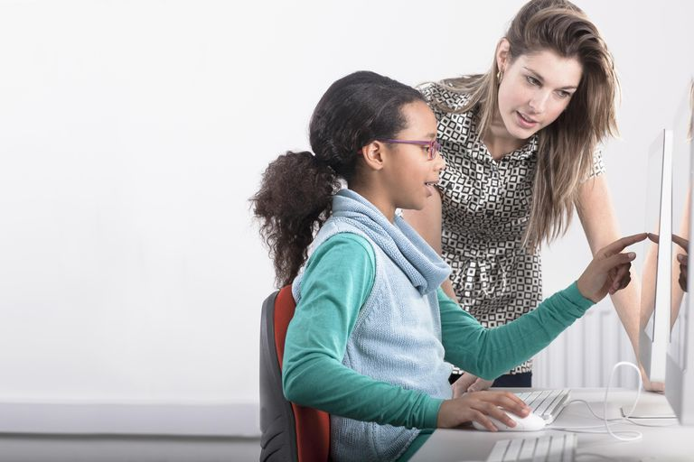 Teacher helping student use computer