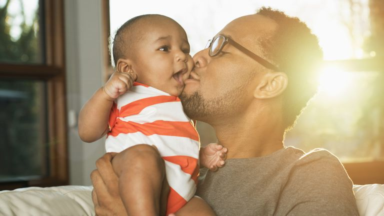 Black father kissing baby son on cheek