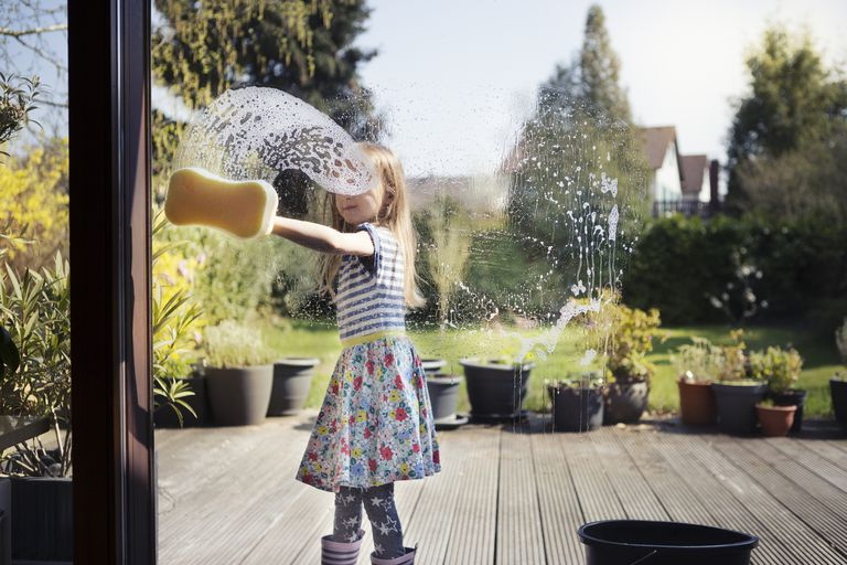 Girl in boots and a dress cleans a window with a soapy sponge