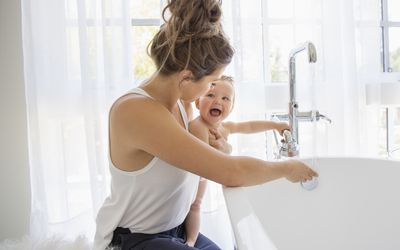 Mother and playful baby daughter preparing bath
