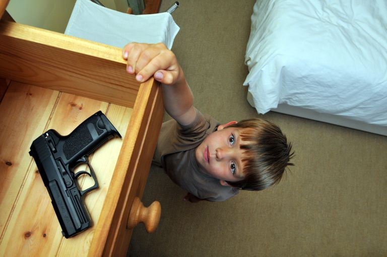 kids and gun safety - boy reaching drawer for handgun