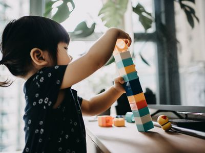 asian toddler girl stacking colorful blocks