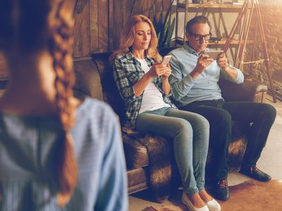 parents busy on smartphones while young child waits for attention