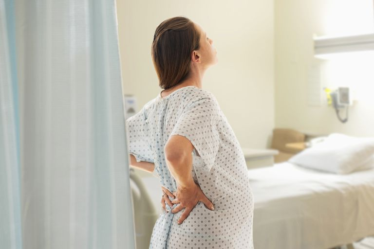Pregnant woman at hospital holding lower back