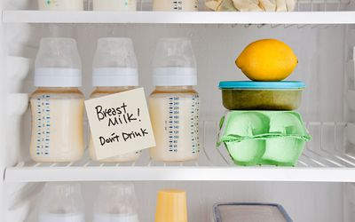 Bottles of breast milk in the refrigerator with sign that says don't drink