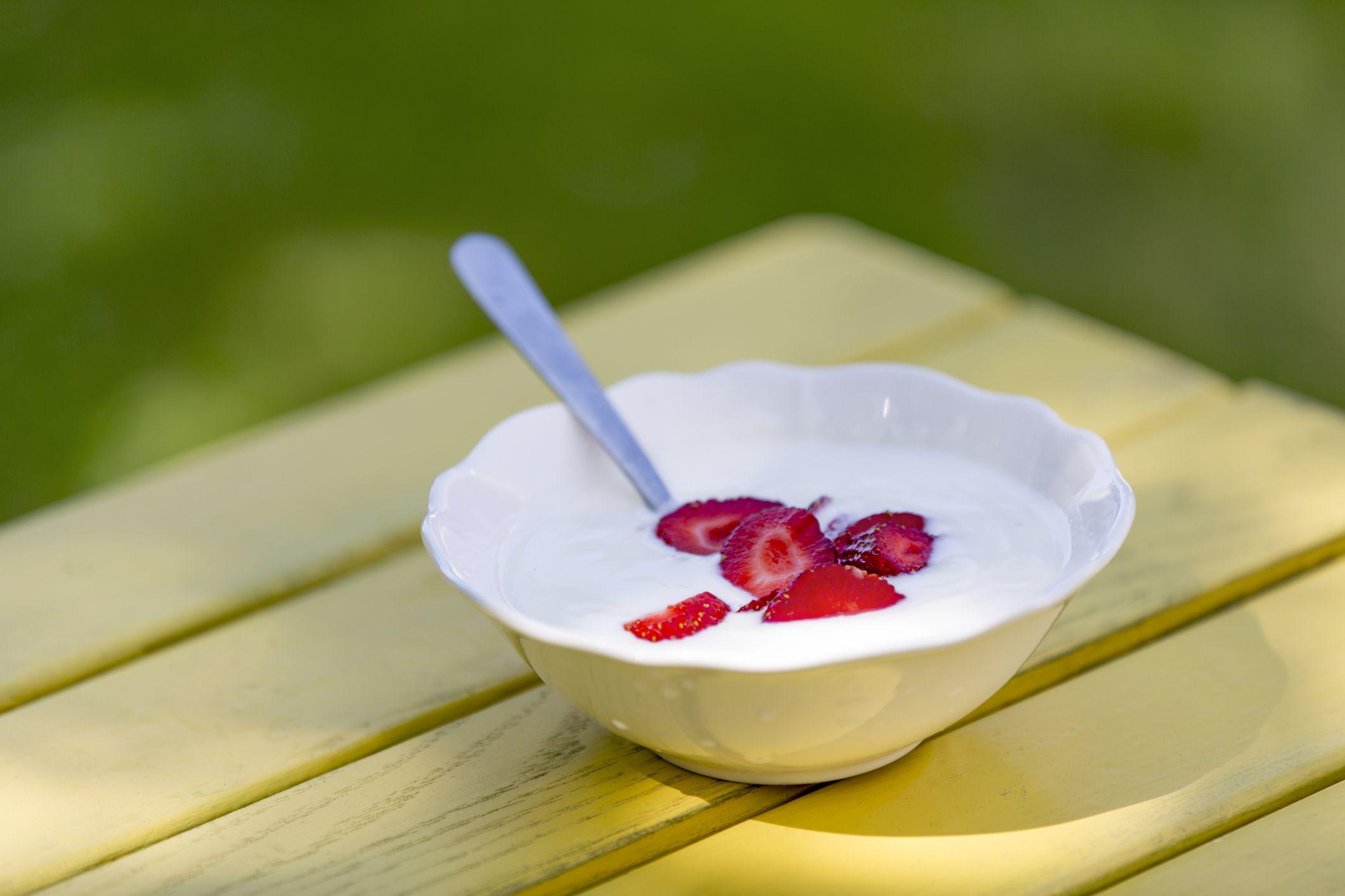 Bowl of yogurt with sliced strawberries