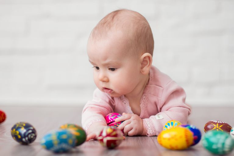 Little baby on stomach playing with painted eggs, metaphor for egg donor conception and choice