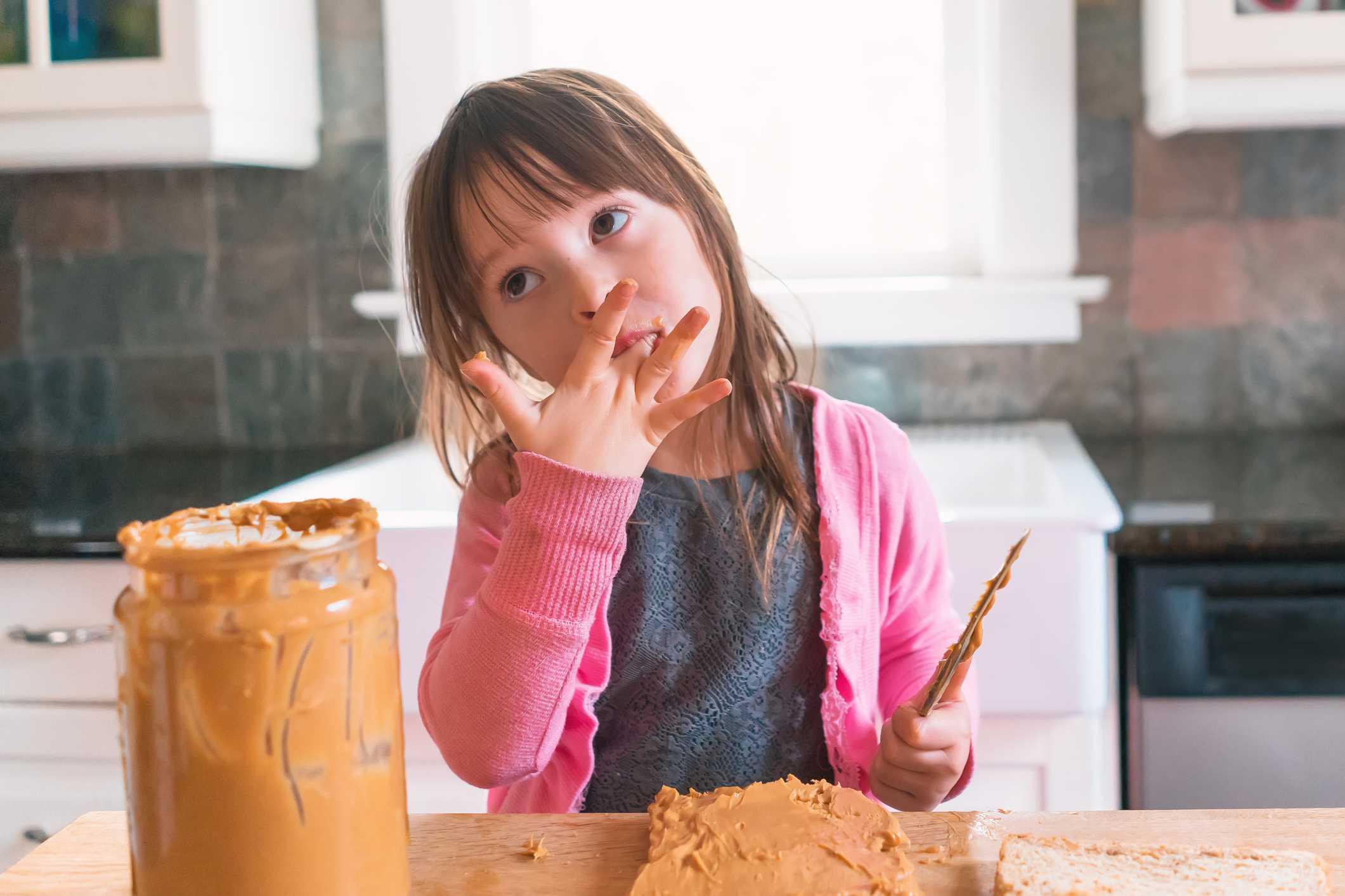 Little girl making peanut butter sandwich