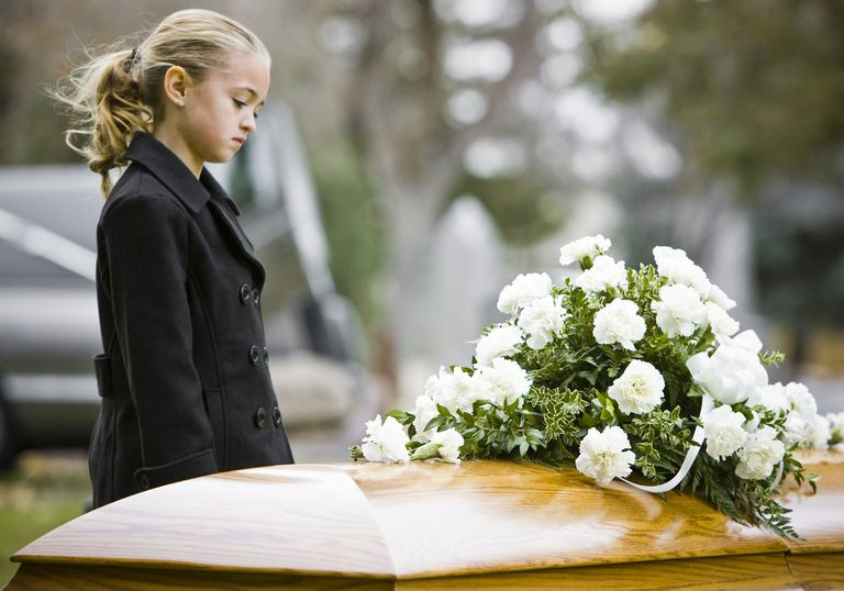 children and grief - girl at coffin at burial