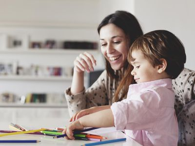 Young mother help her son with drawing