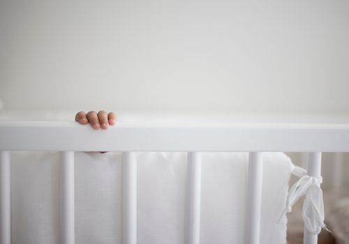 Cropped Image of Baby Hand In Crib At Home