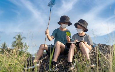 two boys looking at nature wearing bucket hats and masks