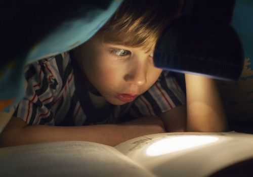 child reading a book in bed