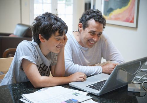 Father and son smiling while working at laptop