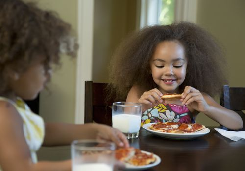 Young girls eating pizza at a table