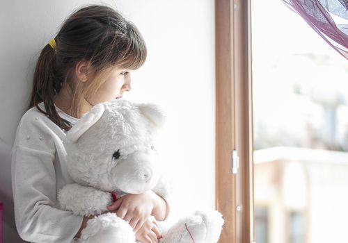Little girl bored at home with her teddy bear