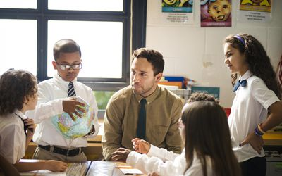 Teacher helping a group of students with a project