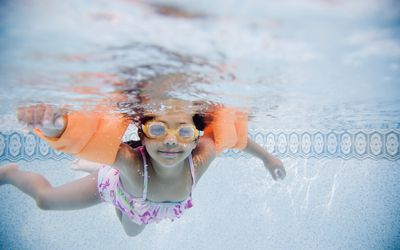 little girl swimming wearing floaties