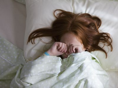 Sleepy Caucasian girl laying in bed