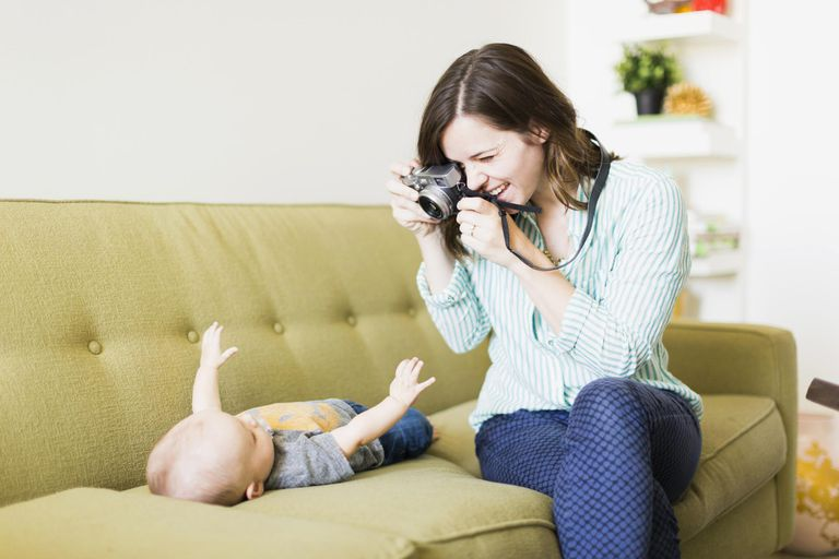 Mother sitting on sofa photographing baby boy